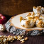 baked brie on a natural cutting board with nuts and an apple