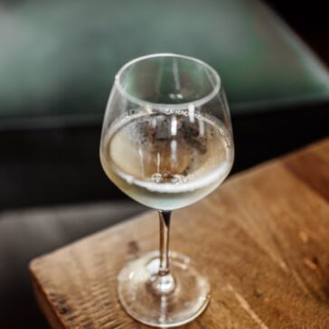 glass of white wine on a wooden coffee table