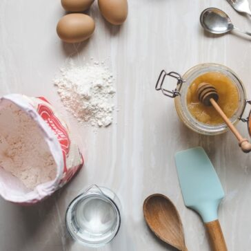bag of flour, eggs, measuring cups, and cooking utensils on the counter