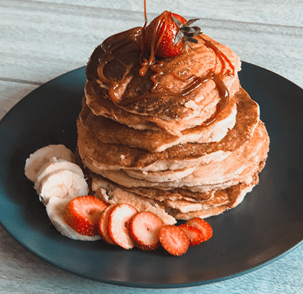 stack of pancakes drizzled with fruit syrup
