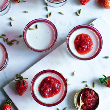 dishes willed with jelled milk dessert with fresh strawberries and strawberry jam