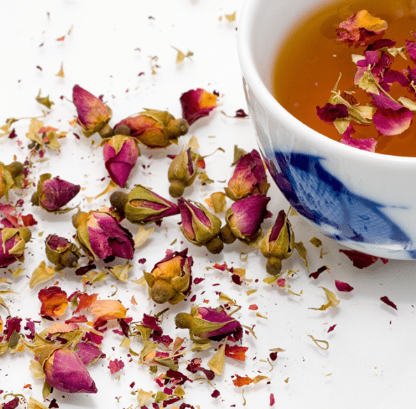 scattered rose petals and a cup of rose petal tea