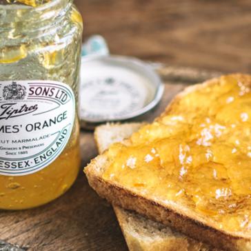 orange jelly jar next to a piece of toast with jelly on it