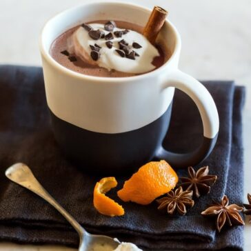 cup of hot cocoa with shaved oranges and chunks of chocolate nearby