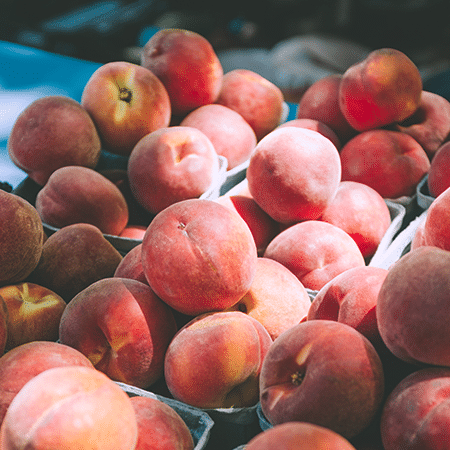 bushels of peaches on a table with a stream of light shining on them