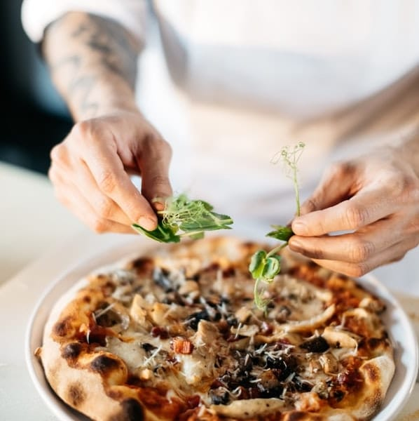 chef adding herbs to a fig pizza