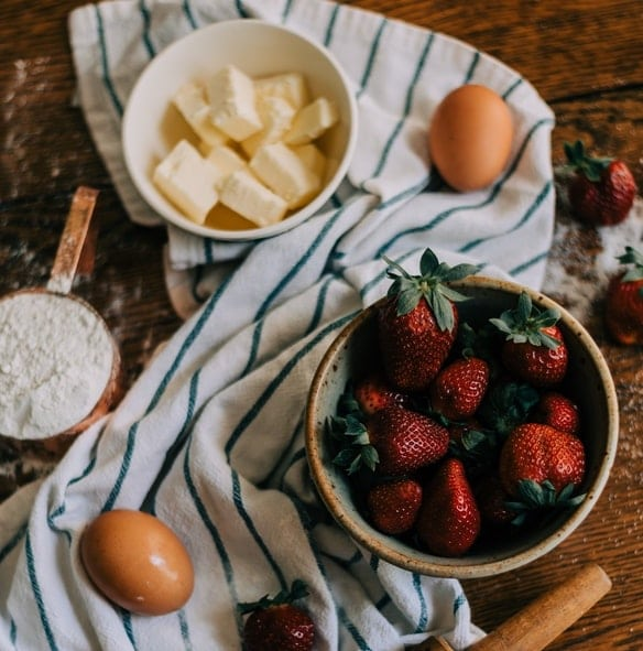 bowls of butter and strawberries on a dish towel on a wooden table