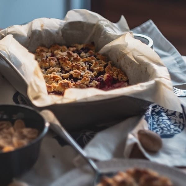 pan of oatmeal jam bars next to a white and blue dish cloth, on a table