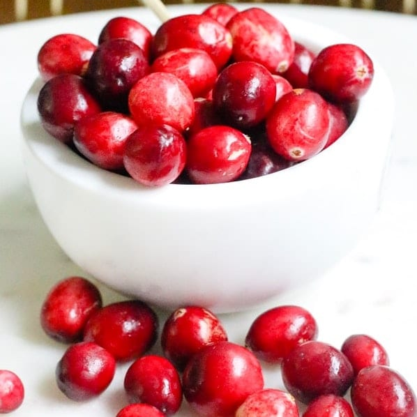 white bowl full of cranberries on a white plate