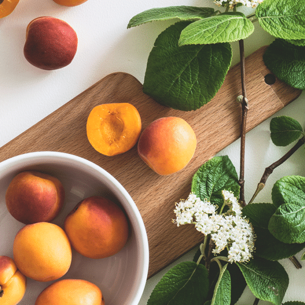fresh apricots in a white bowl and on a cutting board
