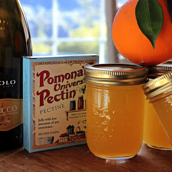 a bottle of champagne, next to a box of Pomona's Pectin, jelly jars and a fresh orange