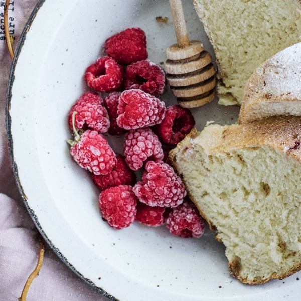 fresh raspberries on a white plate next to fresh bread and a honey comb