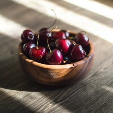 wooden bowl full of cherries on a table in the streaming sunlight
