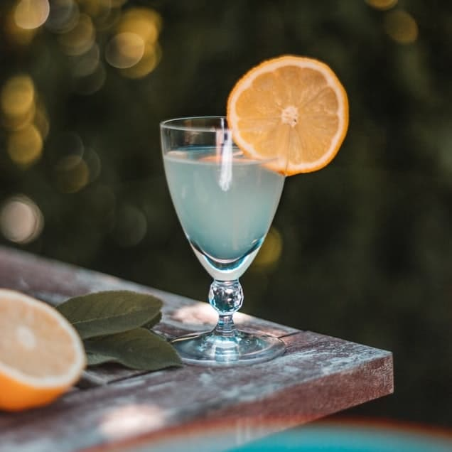 outdoor table with a glass of margarita and a side of citrus