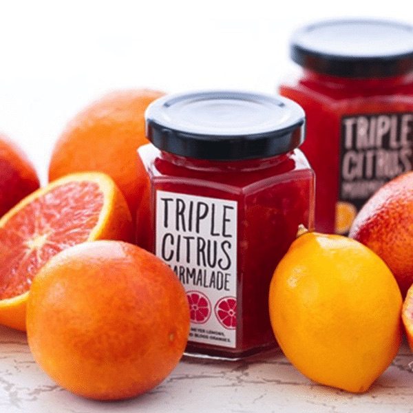 jars of Triple Citrus Marmalade on a table with fresh citrus