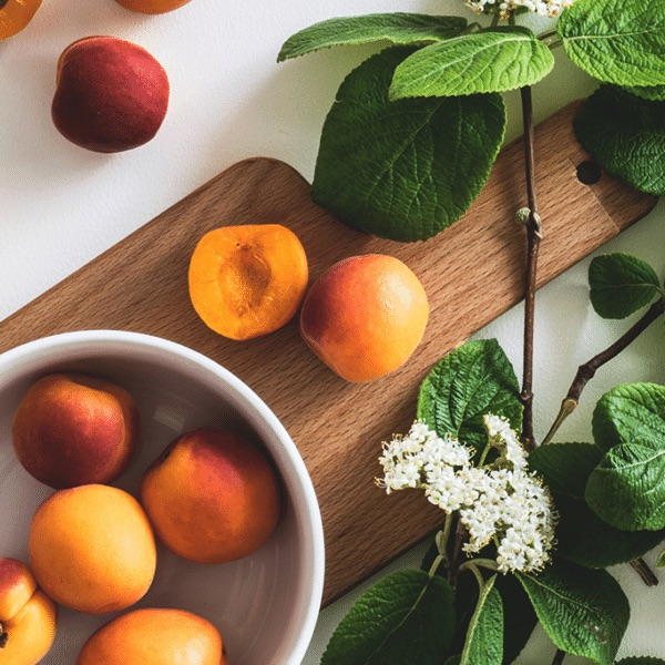 fresh apricots in a bowl next to white flowers and greenery