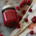 jar of raspberry jam on a tray next to fresh berries