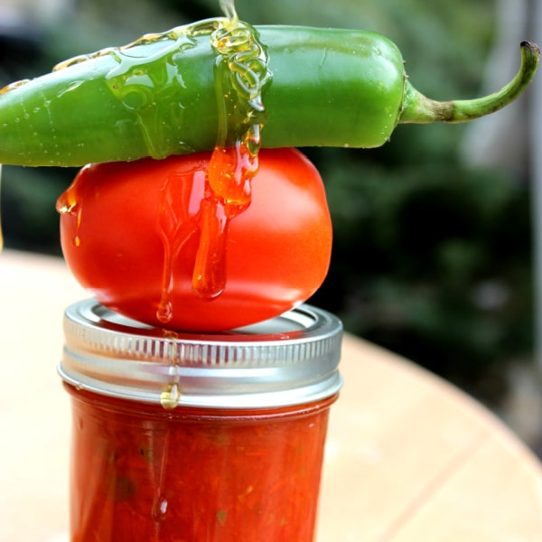 jar of tomato jam with a tomato, jalapeno and honey drizzle on top
