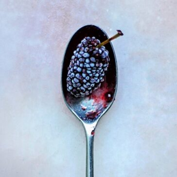 blackberry on a silver sppon on a marble counter top