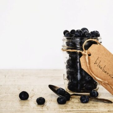 """small mason jar filled with blueberries and tag that reads """"blueberries"""""""