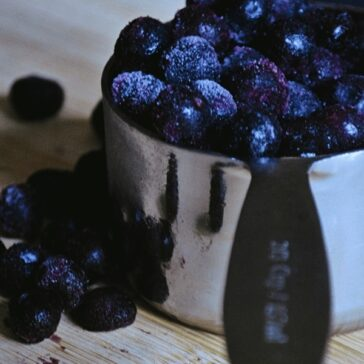 metal measuring cup overflowing with frozen blueberries