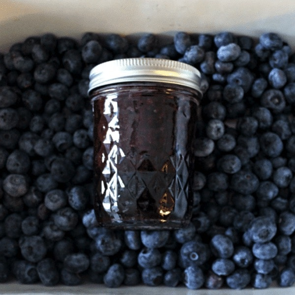 tin full of fresh blueberries with a jar of blueberry jam on top