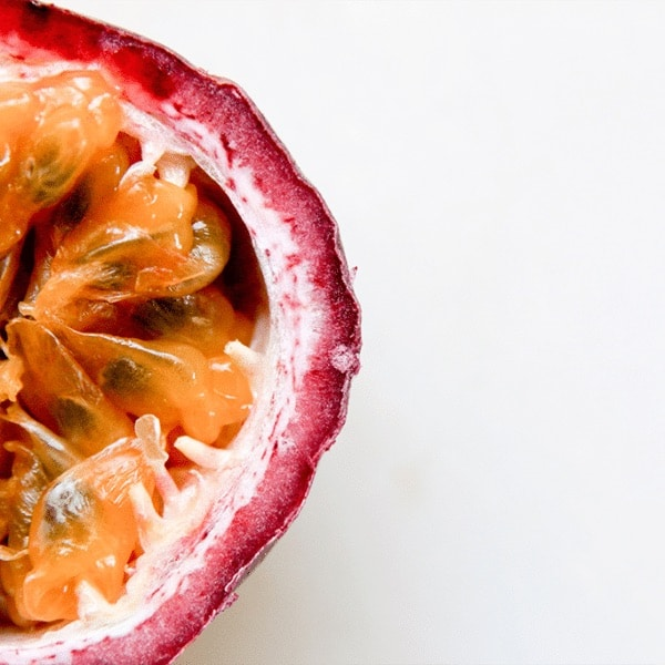 sliced open passion fruit on a white table.
