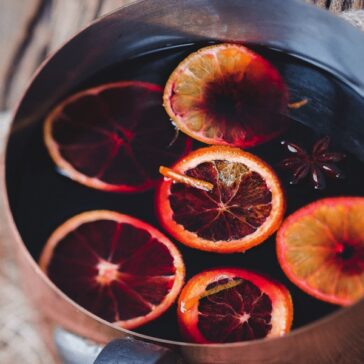 pot of sliced citrus floating in mulled merlot with spices