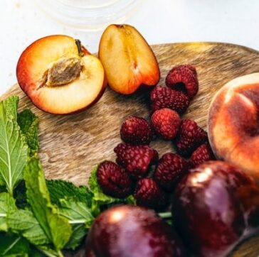 peaches and raspberries on a wooden cutting board