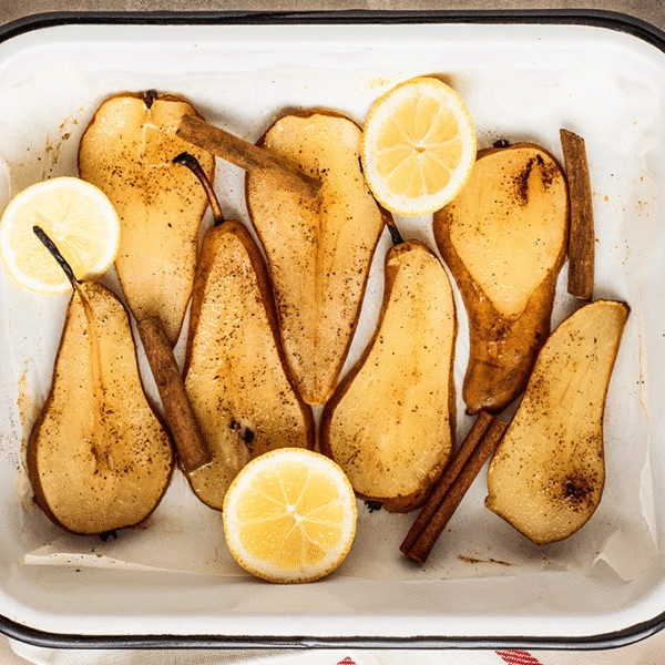 Container of halved pears with fresh lemons and sprinkled with cinnamon