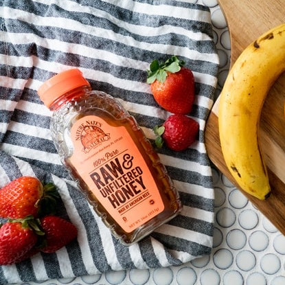 strawberries, bottle of raw honey and a banana on a striped dish towel