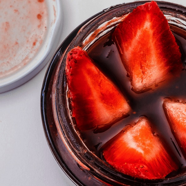 quartered strawberries in a jar of red fruit juice