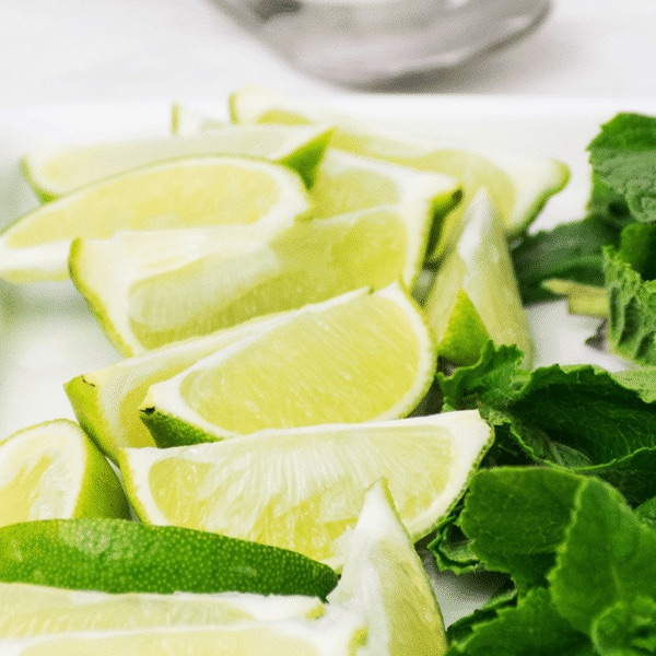 sliced limes and bright green mint on a white countertop
