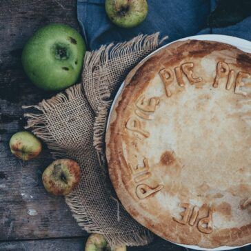 apple pie on a rustic table surrounded by apples