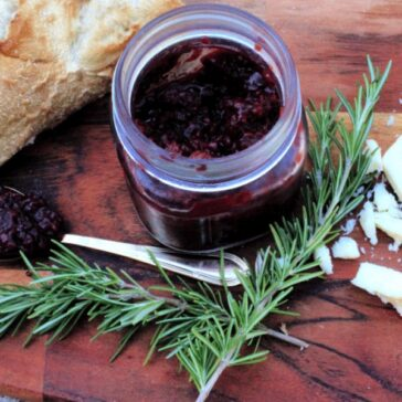 blackberry jam surrounded by french bread and rosemary