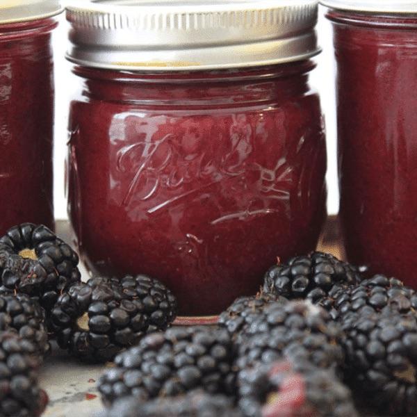 jars of blackberry jam with fresh blackberries in front