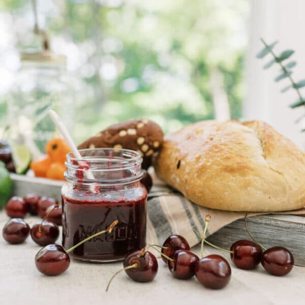 cherry habanero lime jam surrounded by ingredients, bread and culinary tools