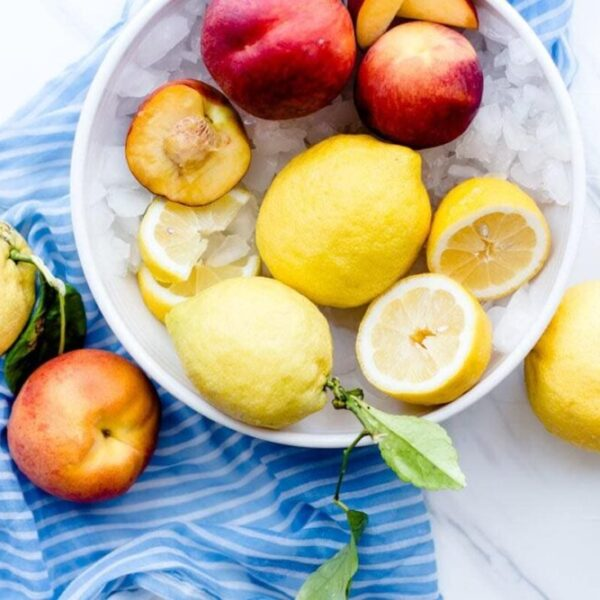 fresh peaches and lemons in a bowl of ice on a blue striped dish towel
