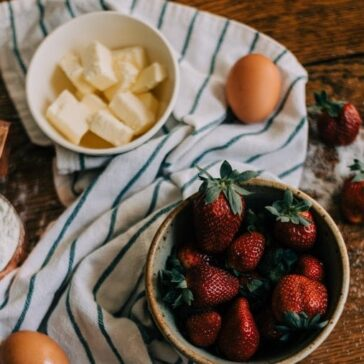 bowl of cubed butter next to a bowl of fresh strawberries surrounded by a kitchen towel